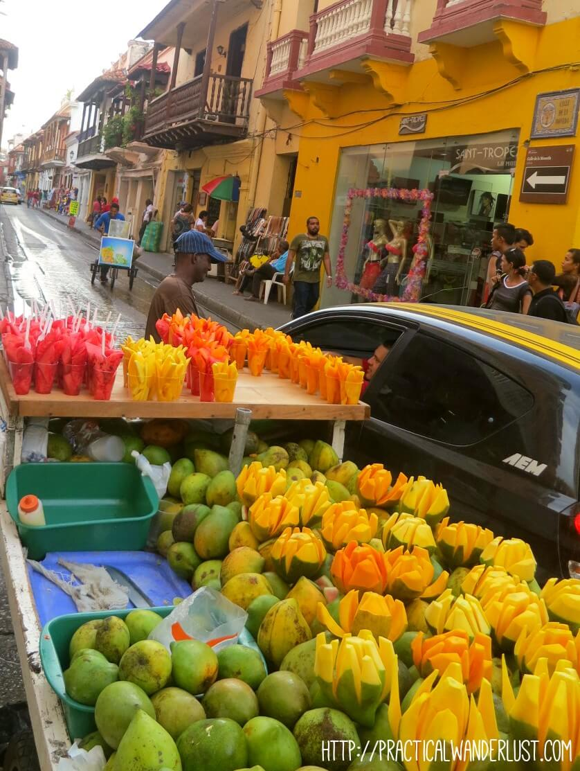 A typical street food cart selling fresh fruit in Cartagena, Colombia.