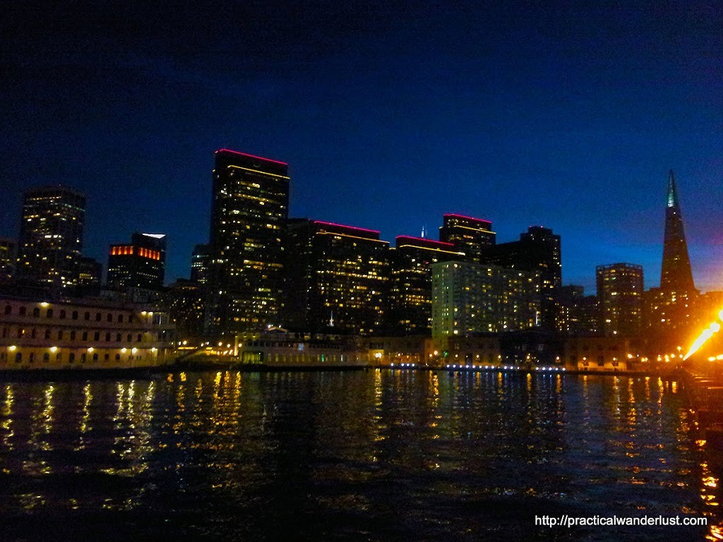 The San Francisco skyline at night, with lights reflected in the water.