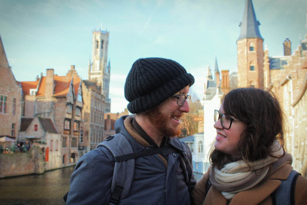 Travel couple at the Rozenhoedkaai in Brugges, Belgium in the winter during our grown up gap year.
