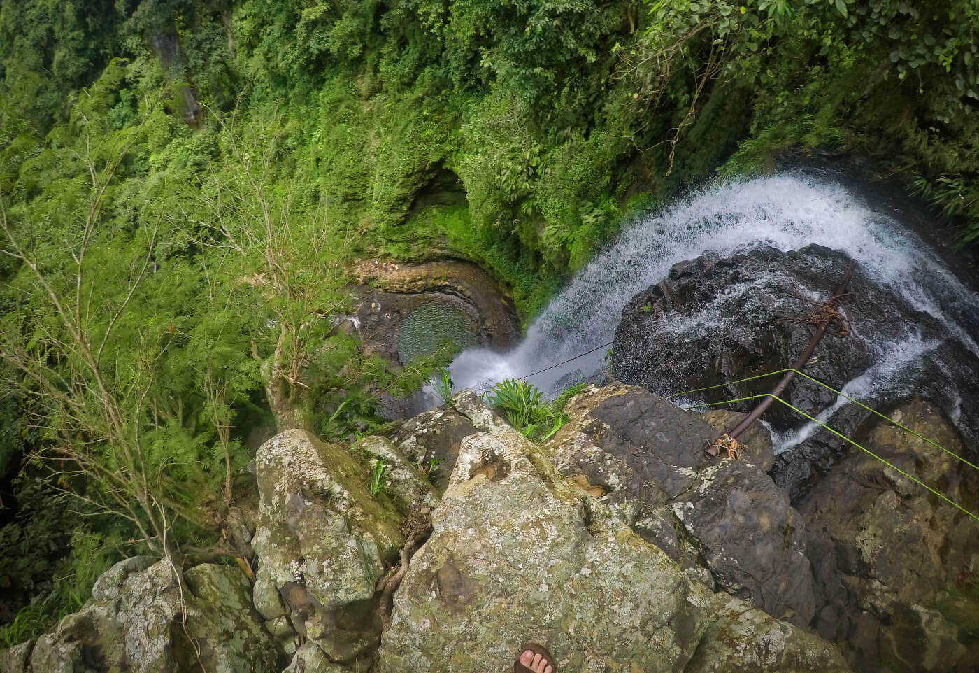 Peering into the depths from Juan Curi Waterfall in San Gil, Colombia before waterfall rappelling down.