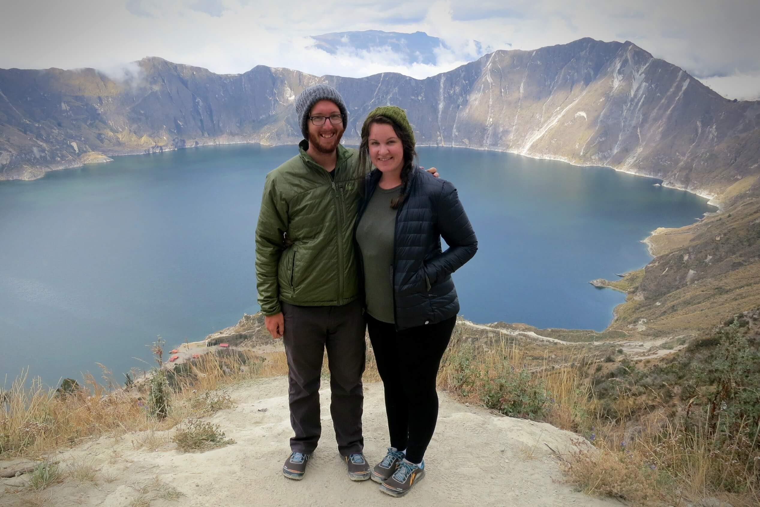 Lia and Jeremy, the owners of PracticalWanderlust.com, wearing obnoxiously matching outfits in front of the Quilotoa Lake in Ecuador.