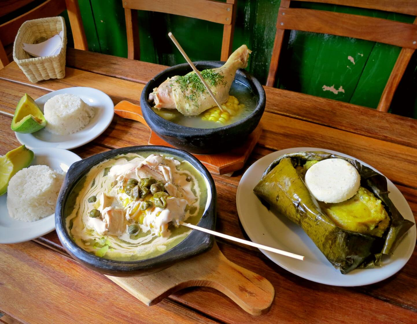 Ajiaco soup, sanchocho, and a giant Colombian tamale with a fluffy arepa! Ajiaco, sancocho, and arepas are all on our list of what to eat in Colombia.