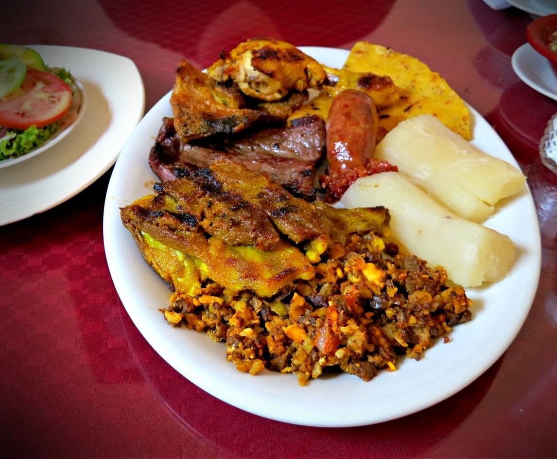 A heaping plate of cabro, sausage, steak, and steamed yuca in Barichara, Santander, Colombia. Cabrito, or baby goat, is cute but delicious, and tops our list of what to eat in Colombia.
