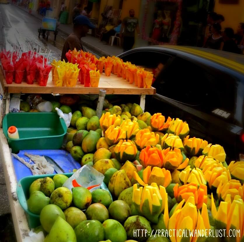 Mangos, papaya and watermelon sold by a fruit vendor in the streets of Cartagena, Colombia. Colombia's delicious fruit tops our list of what to eat in Colombia!