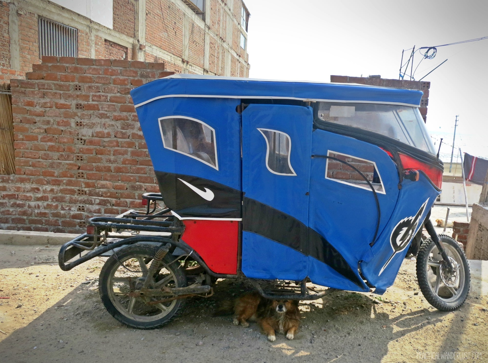 An unfriendly stray dog under a 3-wheeled mototaxi in Huanchacho, Peru. Mean stray dogs and mototaxis were surprises to us when we began backpacking in Peru!