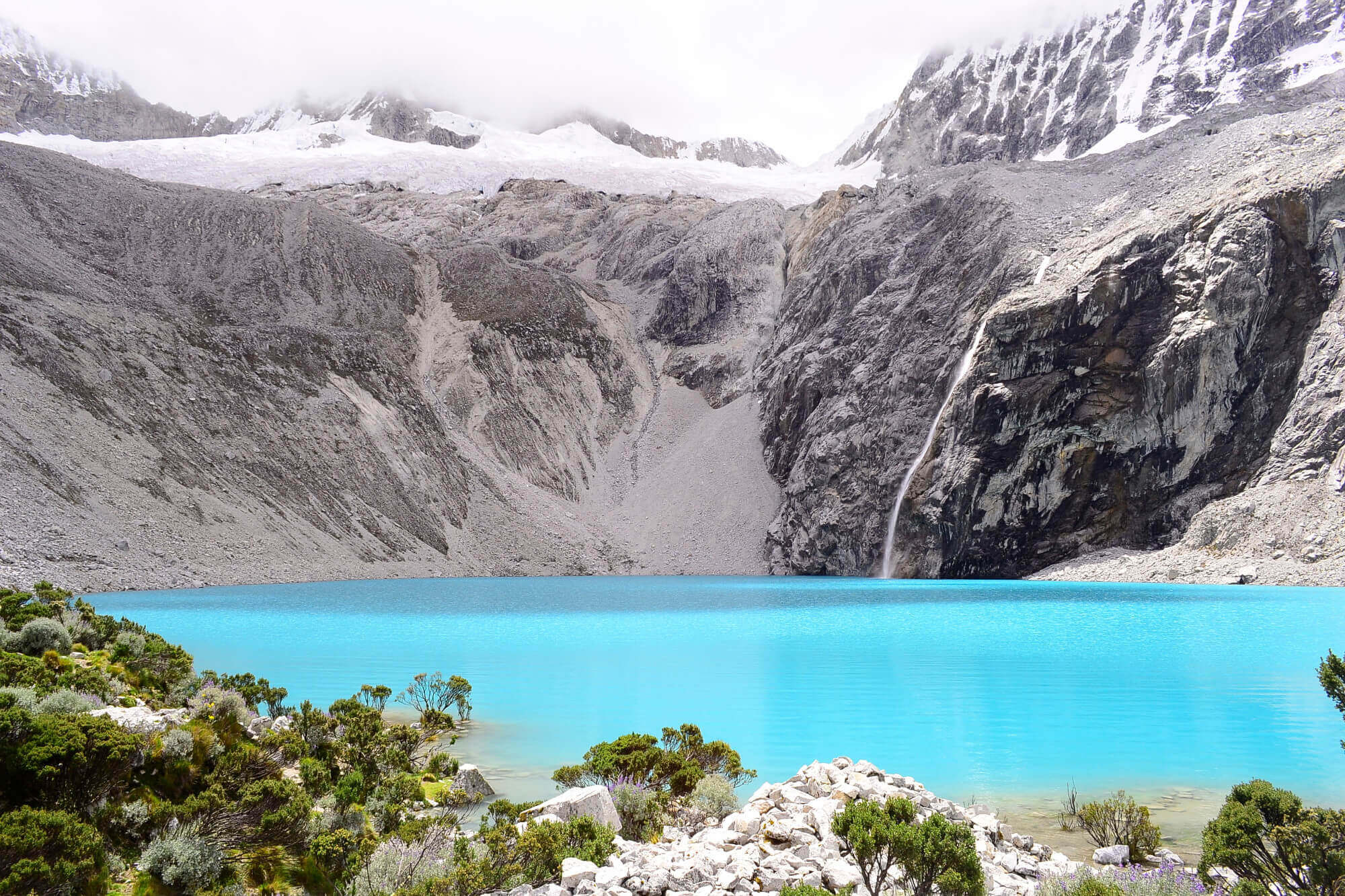 Stunning glacial lake Laguna 69 sits at a grueling 15,000 feet above sea level. The difficult hike is worth the view! Laguna 69 is outside of Huaraz, Peru in the Cordillera Blanca mountain range.