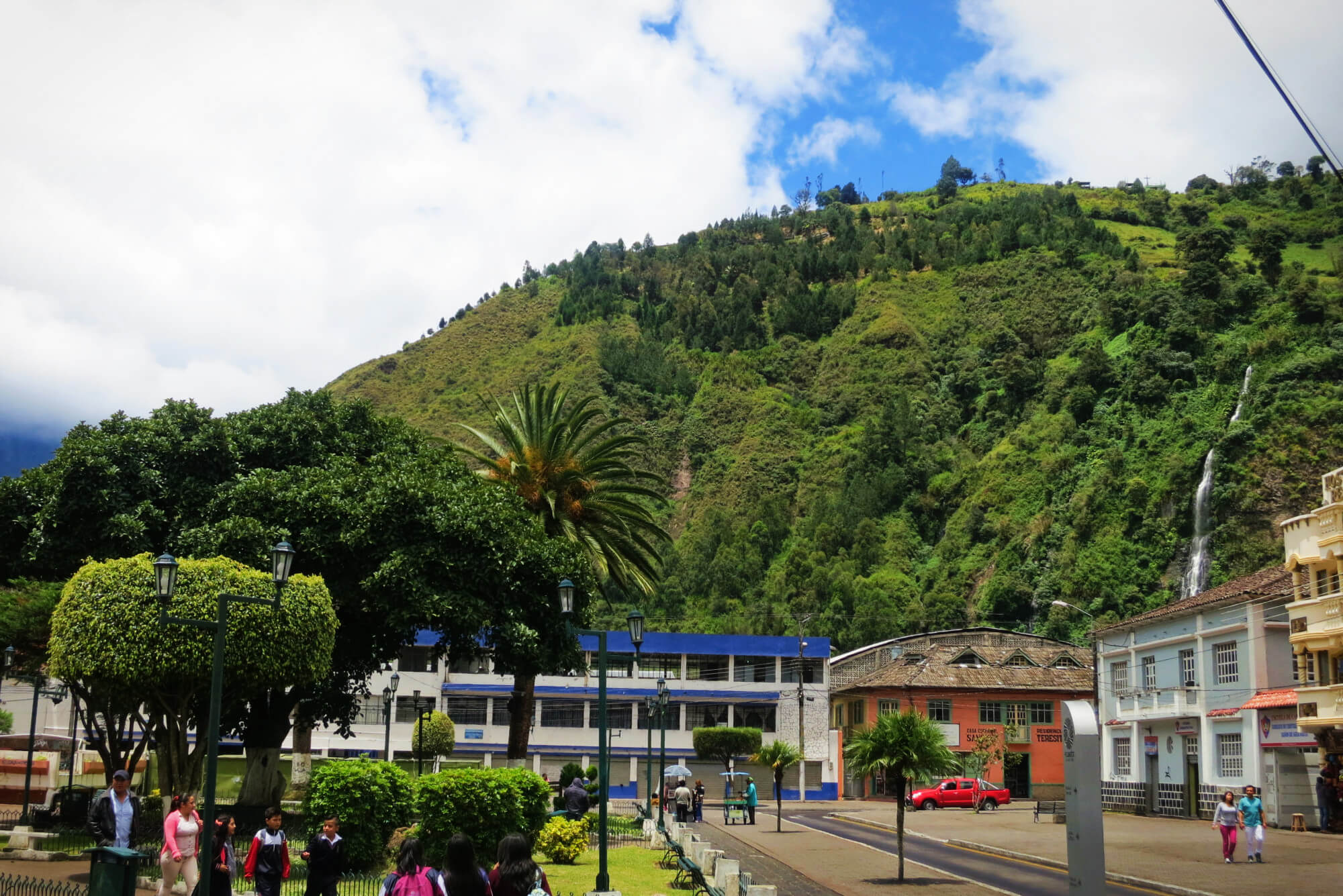 View of the thermal baths at the foot of a giant waterfall in the adventure town of Baños, Ecuador!