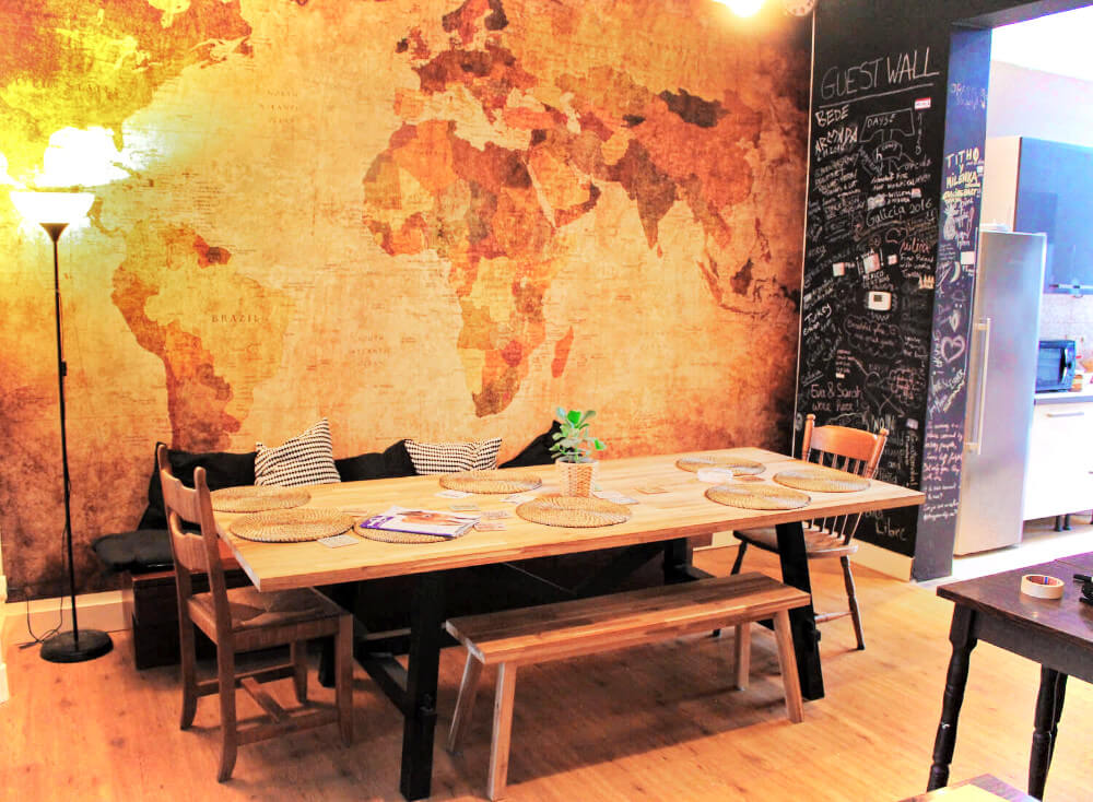 The dining room table with a world map backdrop at Kabas Hostel in Antwerp, Belgium.