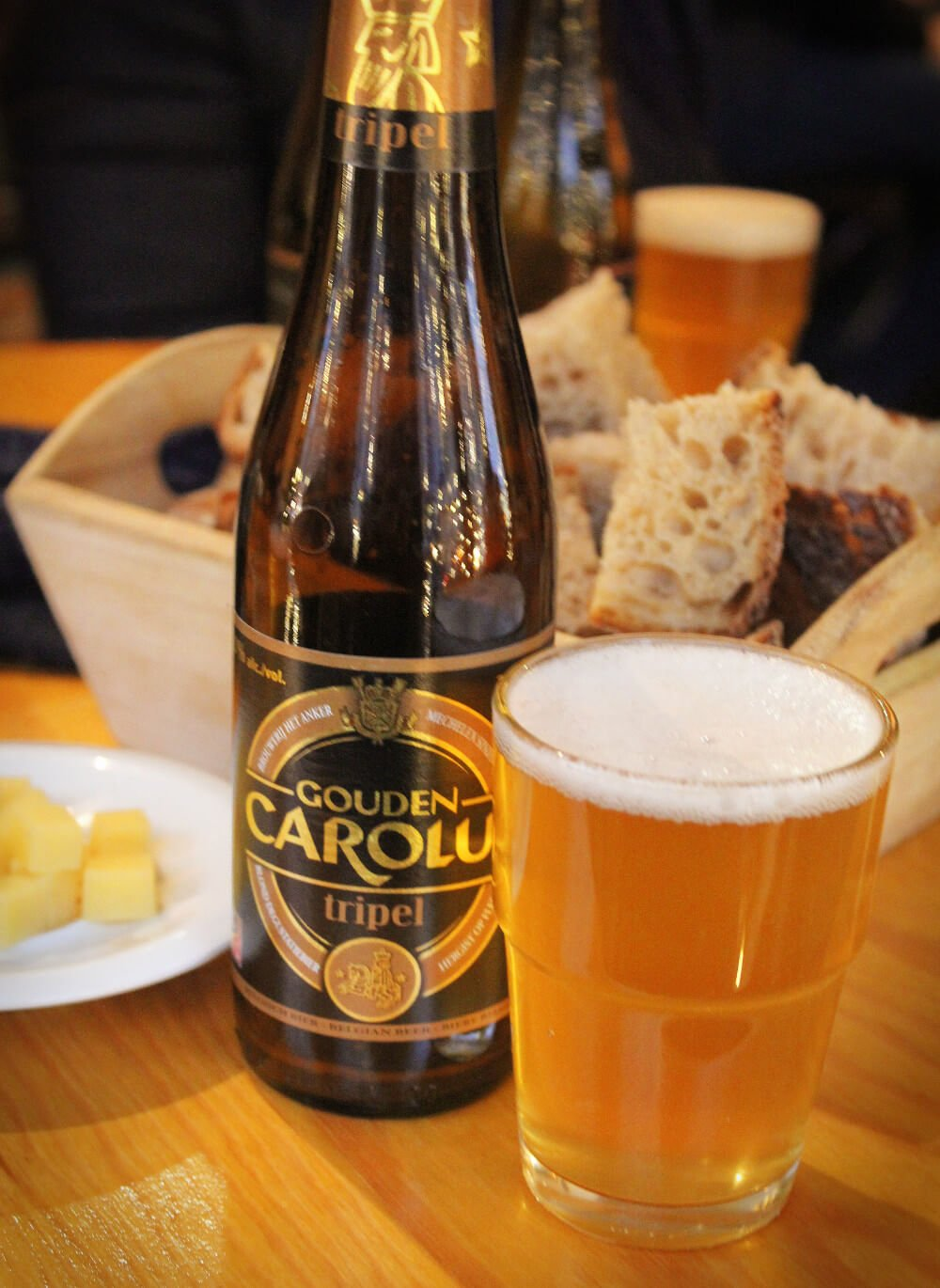 Drinking a tasty Belgian beer with cheese and bread. Not in a Belgian bar, mind you, this is actually in a Belgian beer store. Awesome, right?