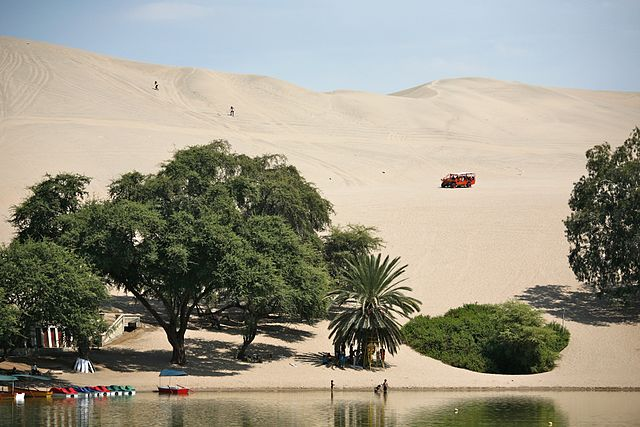 The enormous dunes of Huacachina surround a lush desert Oasis. It's the best place to sandboard in Peru!