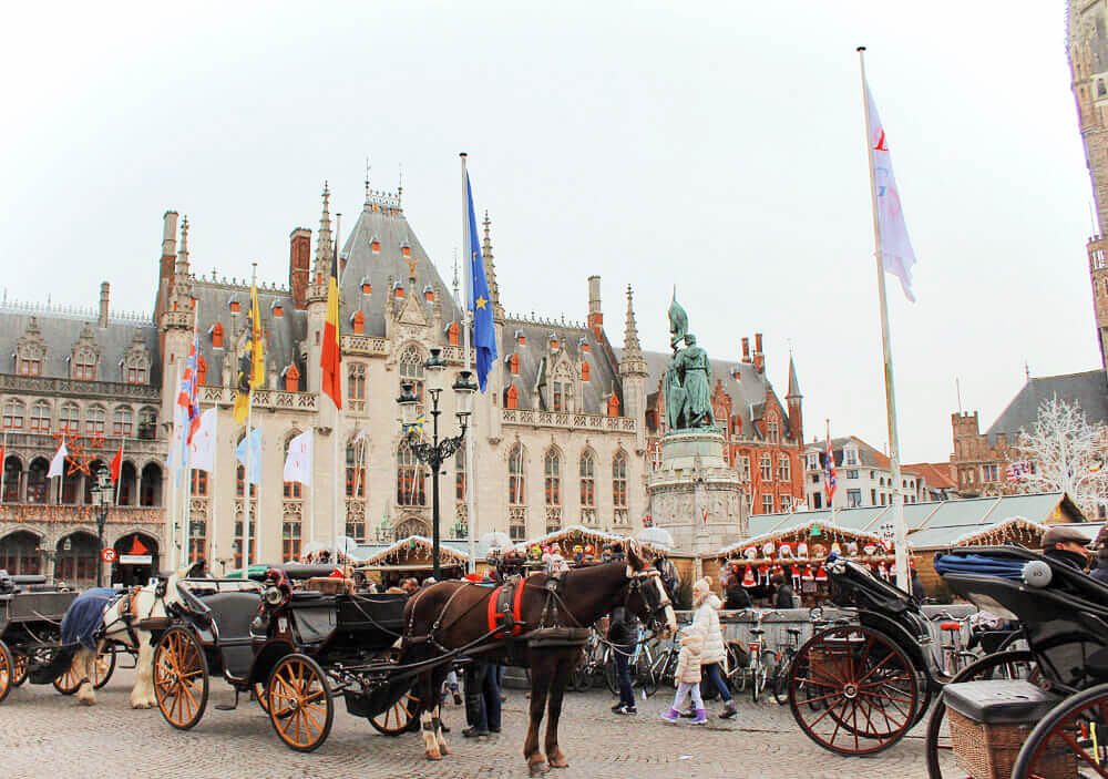 A horse drawn carriages in front of the Christmas Market in stunning Markt Square in Bruges, Belgium in winter. So ridiculously romantic I can't even STAND it!