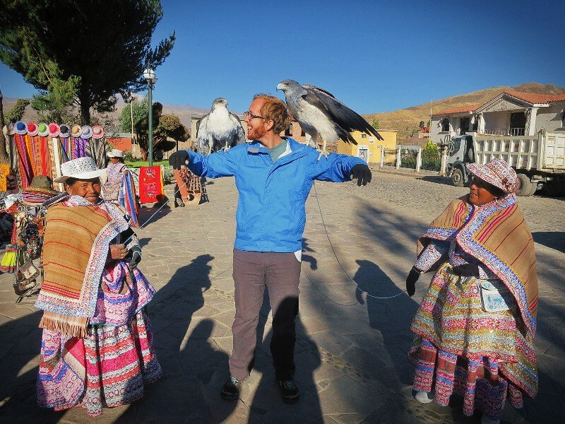 Posing with birds of prey and locals in Arequipa, Peru.
