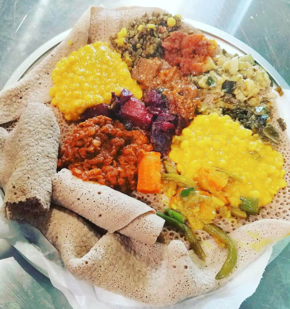 A typical platter of Ethiopian food is served with multiple kinds of meat and veggie dishes on one giant piece of spongy injera bread. The best part is eating the bread underneath after it's soaked up all the sauces! Ethiopian food is a quintessential Oakland cuisine.