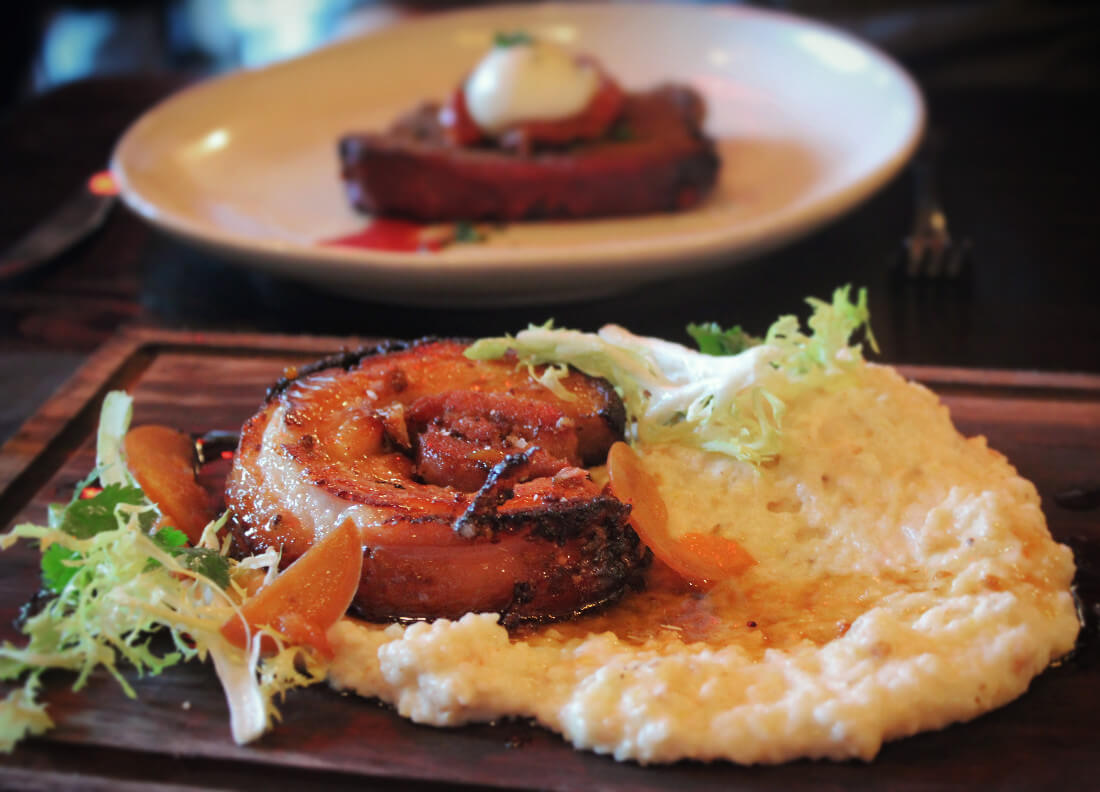 Bourbon and molasses braised pork belly with cheese grits and grilled peaches at The Hatch in Paso Robles, California. Trust us, you do not want to miss this foodie dream spot.