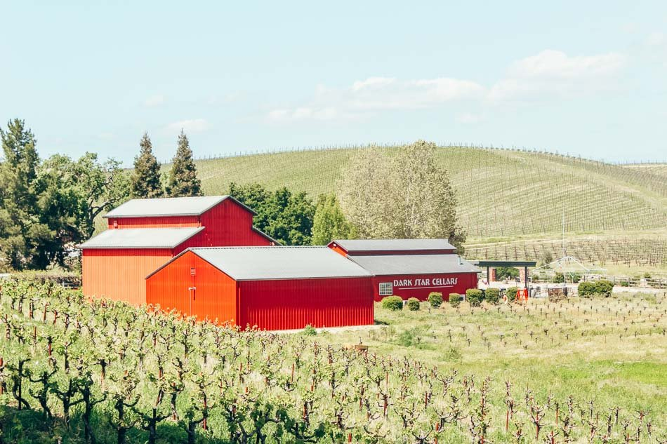 Bright red Dark Star Cellars in a green vineyard in Paso Robles, California.
