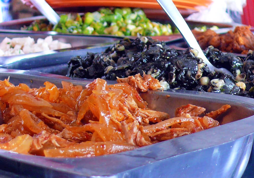 Look past the delicious spicy tinga in the foreground to that sad, gray-looking goop behind it. That's Huitlacoche, aka corn smut. It's one of the most obscure Mexican foods!