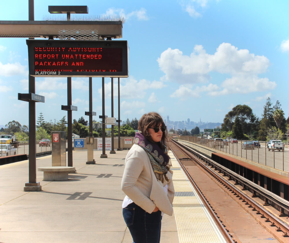 Waiting for BART in Oakland with the tiny San Francisco skyline in the background.
