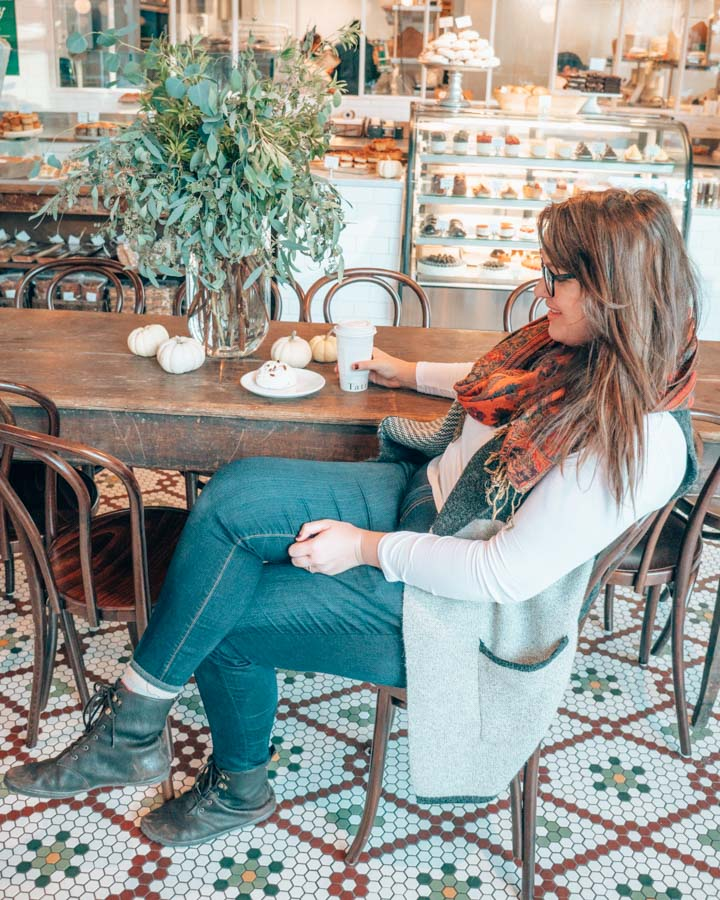 Lia drinking in a coffee shop in Boston wearing jeans and boots.