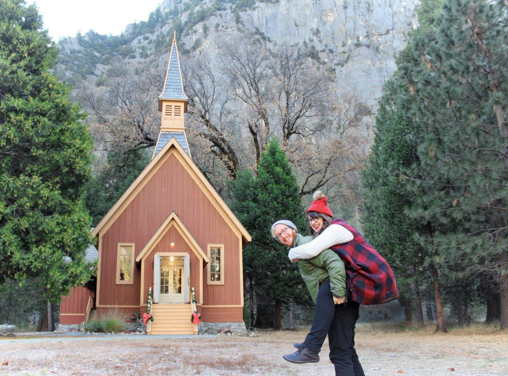 Jeremy gives Lia a piggyback in front of Yosemite Chapel in Yosemite Valley.