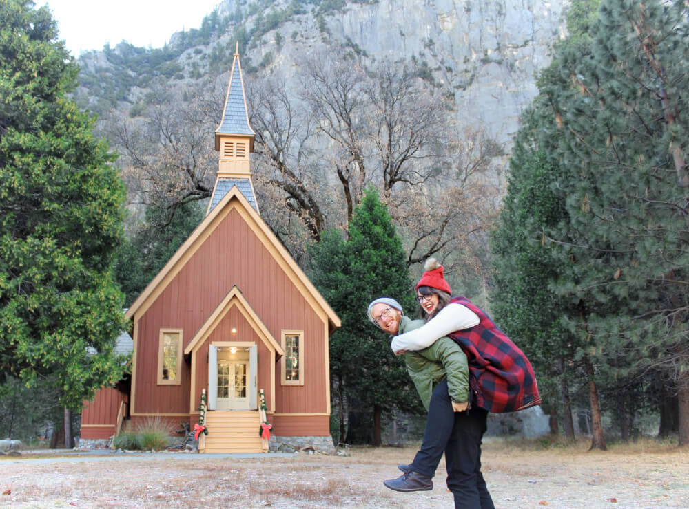 Jeremy giving Lia a piggy back ride in front of the chapel in Yosemite National Park, California, in the winter.