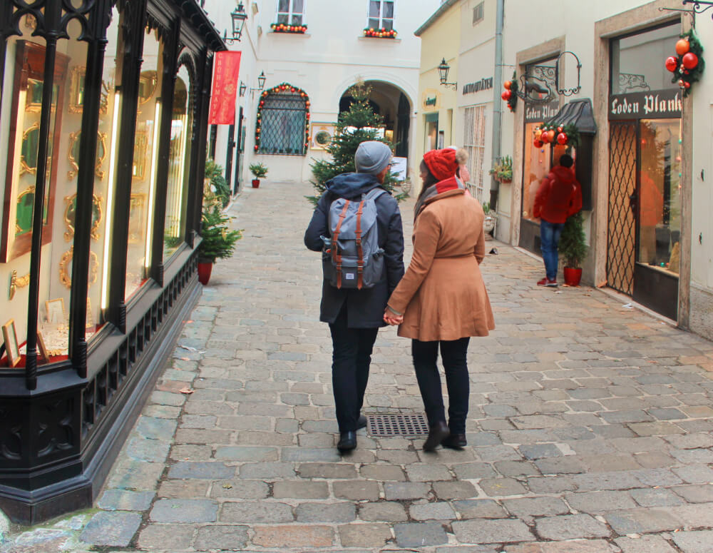 Lia and Jeremy from Practical Wanderlust in an alley in Vienna, Austria in the winter.