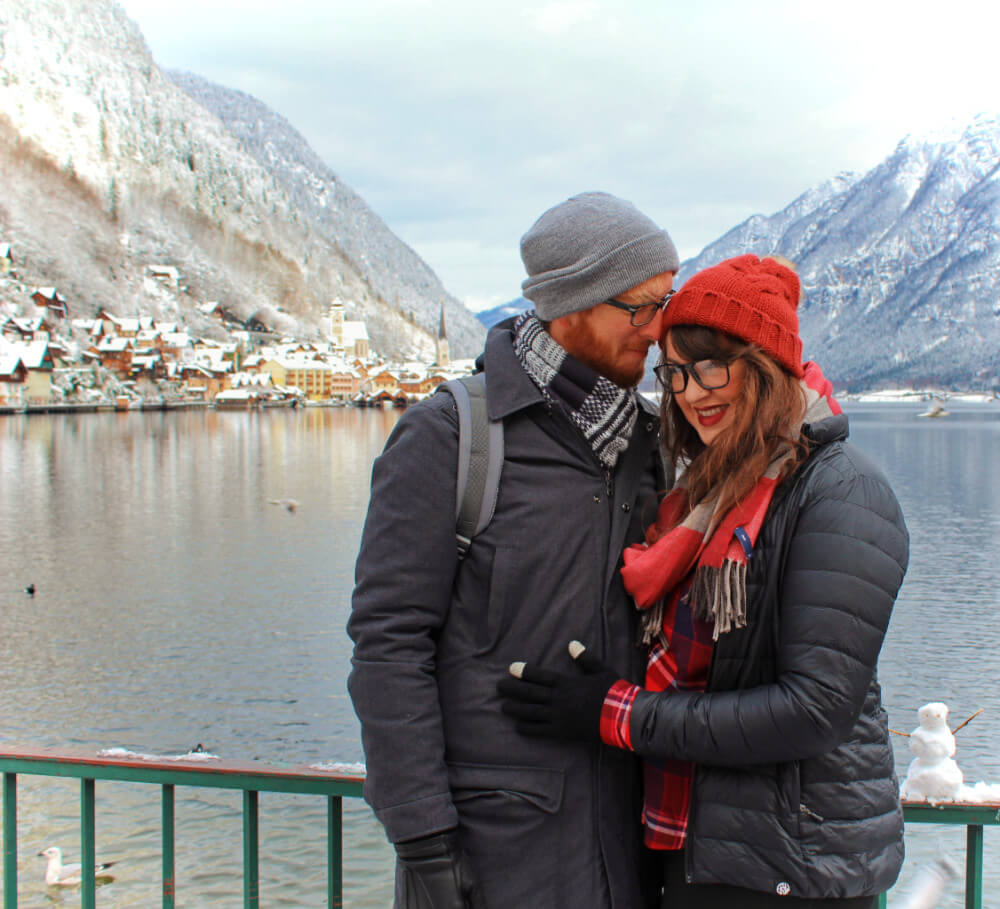 Lia and Jeremy, travel couple from Practical Wanderlust travel blog, in Hallstatt Austria in the winter.