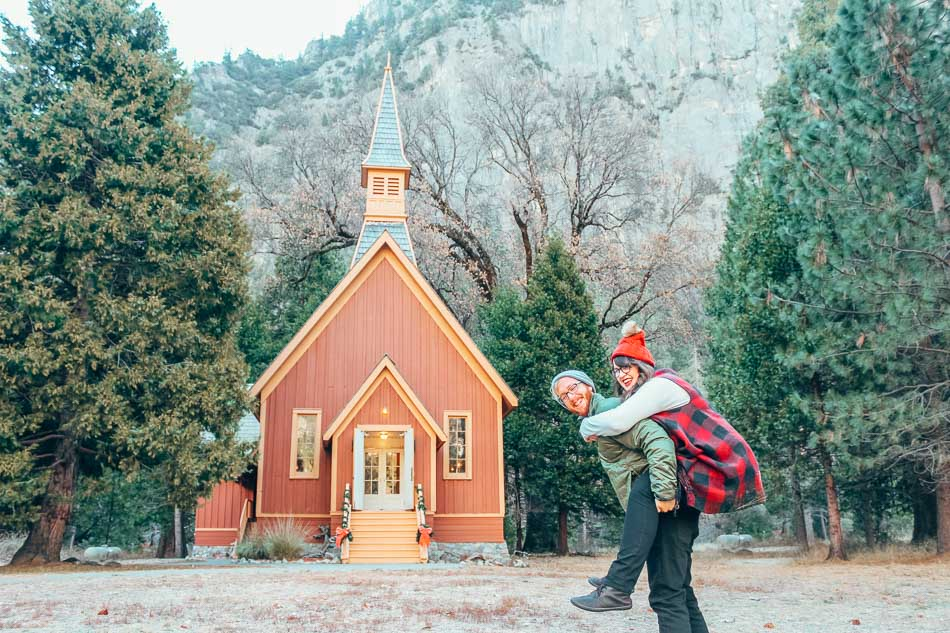 Couple laughing and smiling in front of a small cathedral in Yosemite Valley, Yosemite National Park