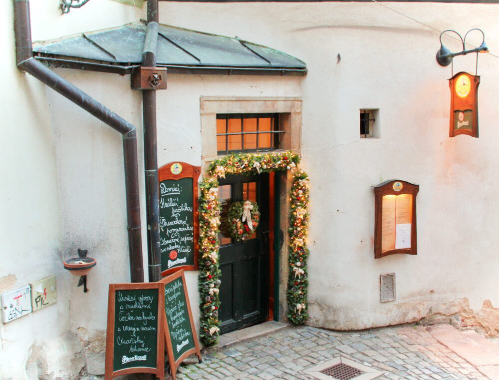 A festive restaurant tucked away in an alley in Cesky Krumlov, Czech Republic, Europe.