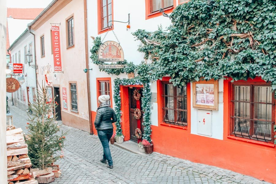 Exploring an alley in Cesky Krumlov with an Alfons Muchas exhibit and crawling ivy.