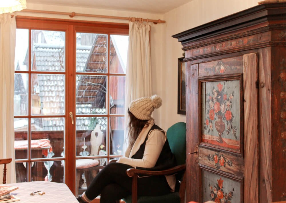 Lia in a hat gazing out of the window of the Bräu-Gasthof in Hallstatt, Austria.
