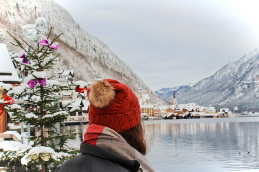 Gazing out over the lake in Hallstatt, Austria next to a decorated Christmas tree.