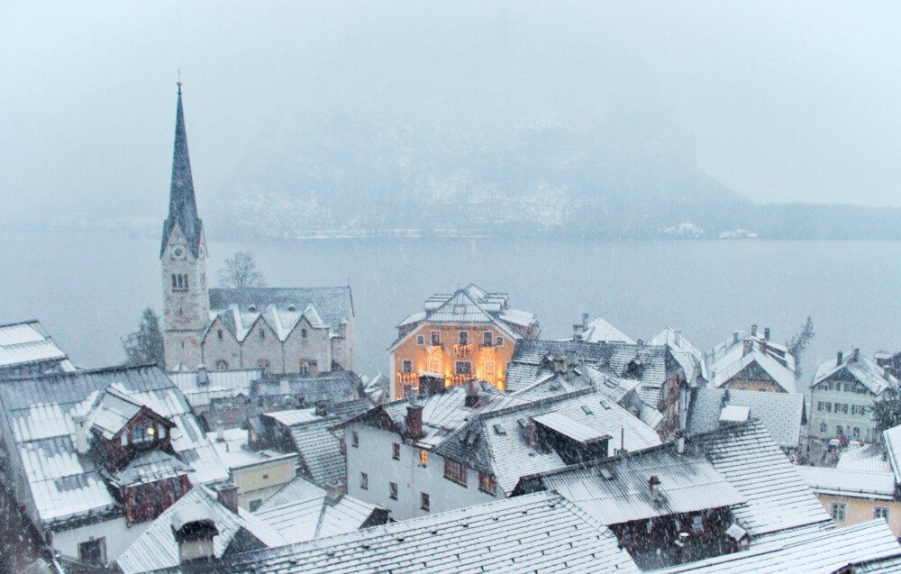 Hallstatt, Austria in the snow and fog as night falls. Mountains, fog, snow, ... this is my literal heaven.