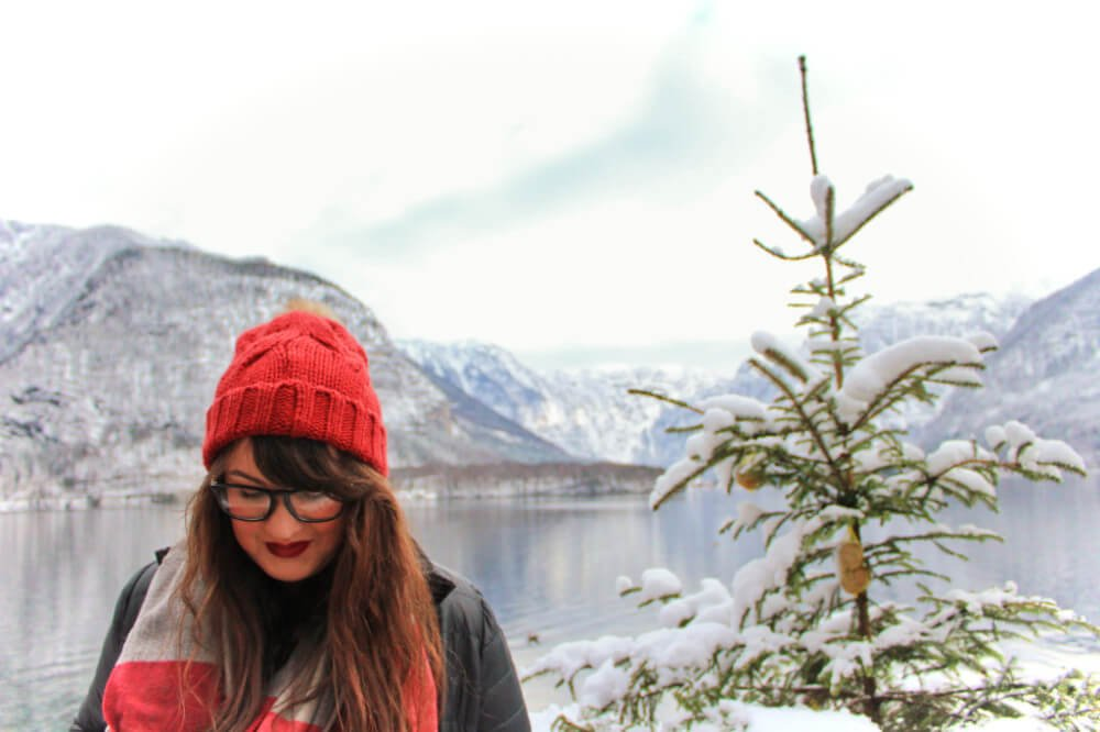 Lia in Hallstatt, Austria in the winter, next to a small Christmas tree and in front of the lake and mountains.