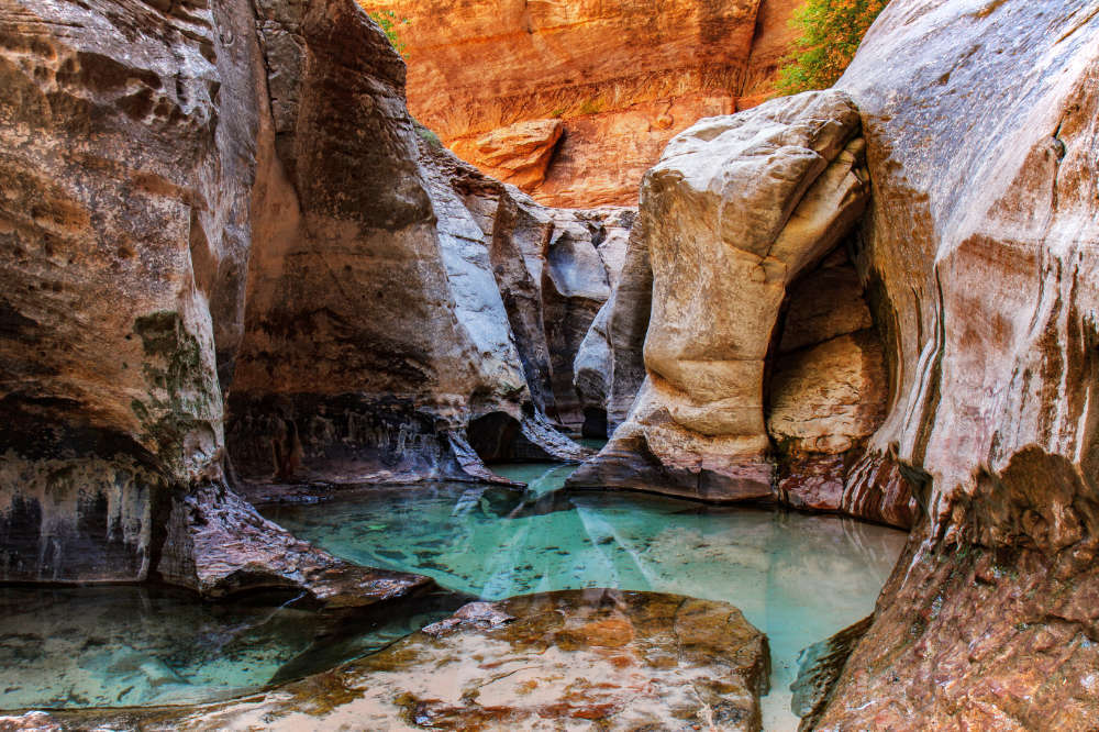 Bright blue pools and carved rock faces in the Subway Hike in Zion National Park.