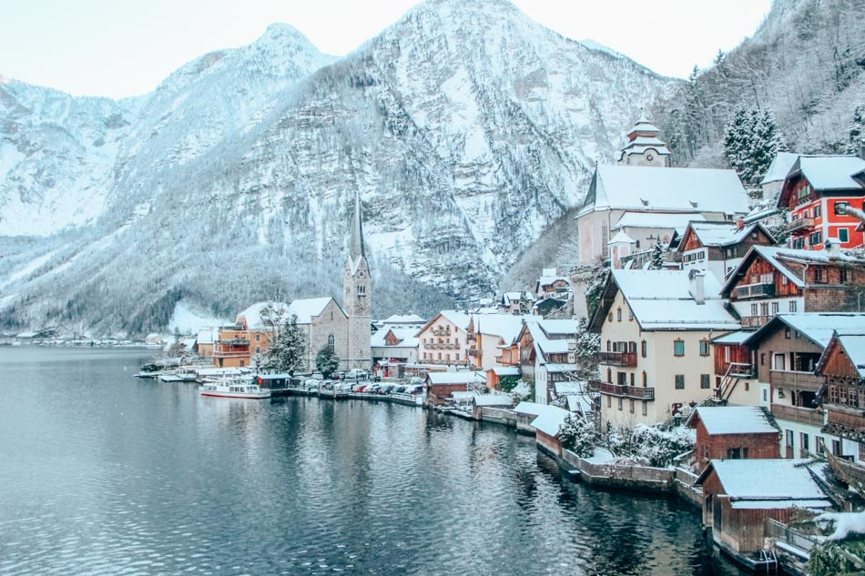 Snowy Hallstatt, Austria in front of a mountain, reflected in the icy lake.