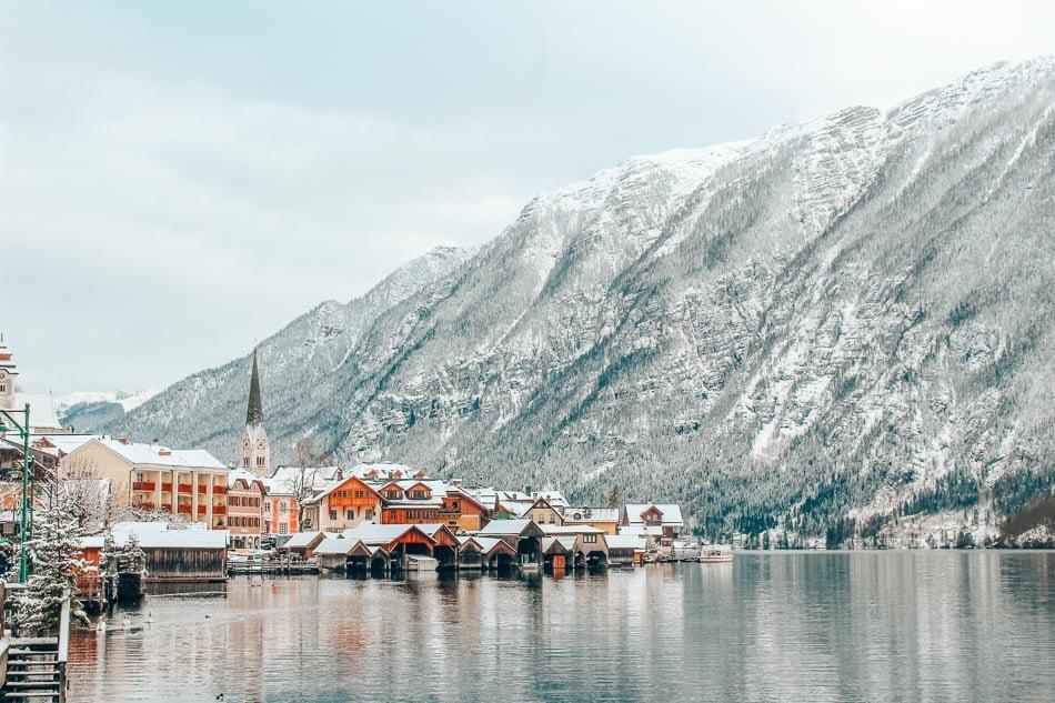 Hallstatt, Austria reflected in the lake beneath a snowy mountain.