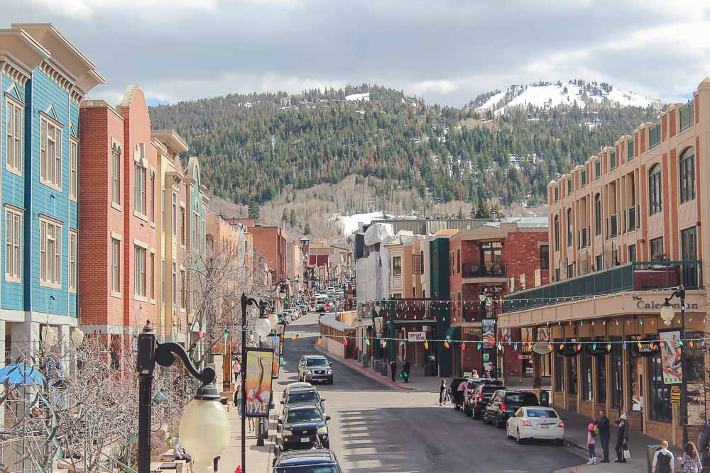 Downtown Park City, Utah in the spring with a snowy mountain in the background.