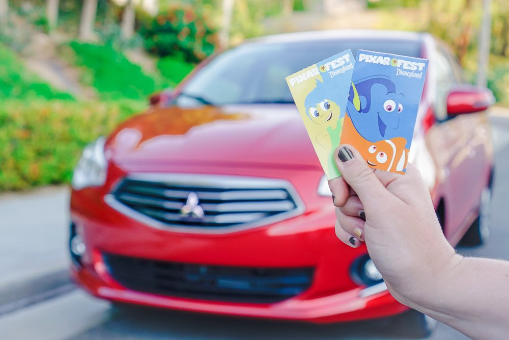 """Start off your Disneyland adventure by snapping a picture of your tickets (or Mickey Bands)! We posed our Pixar Fest tickets in front of our Mitsubishi rental car for the perfect """"road trip to Disneyland"""" photo op!"""