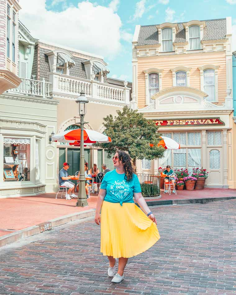 Lia wearing blue and yellow and white allbirds shoes at Disney World.