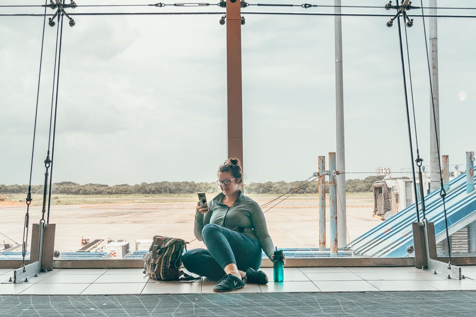 Lia on her phone in an airport.