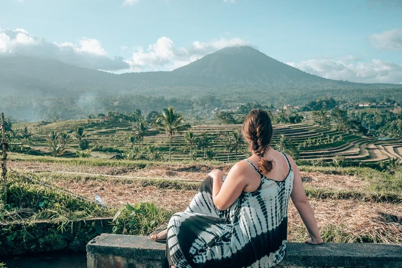 Lia looking out over rice terraces and a volcano in Bali, Indonesia.