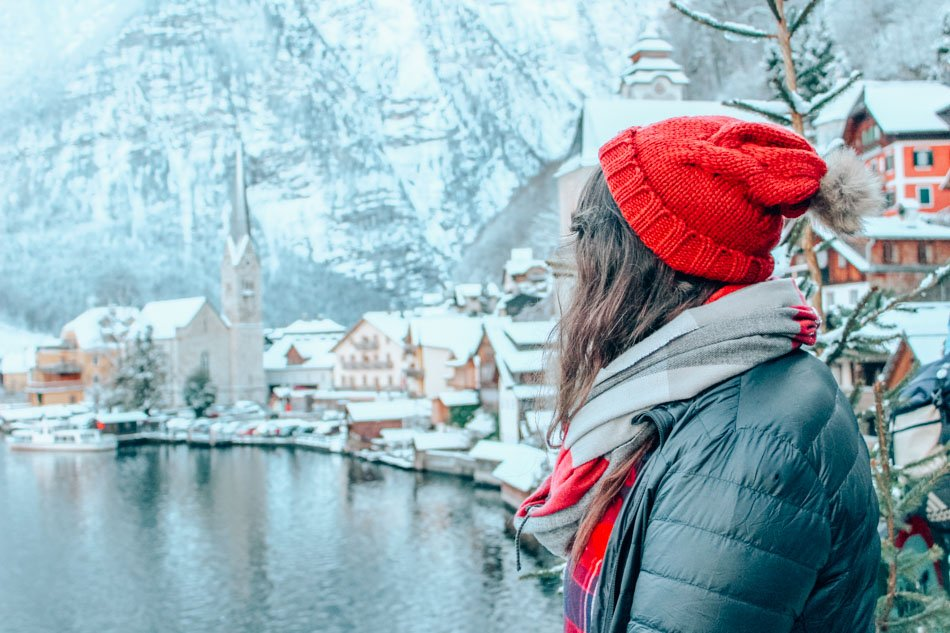 Lia in a red hat looking at Hallstatt, Austria in the snow in the winter.