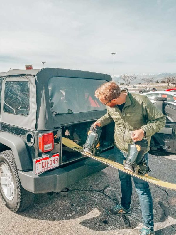 Jeremy loading up a jeep with his rented snowboard.