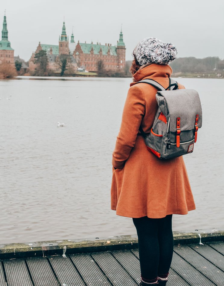 Lia and her backpack in her coat looking at a castle near Copenhagen.