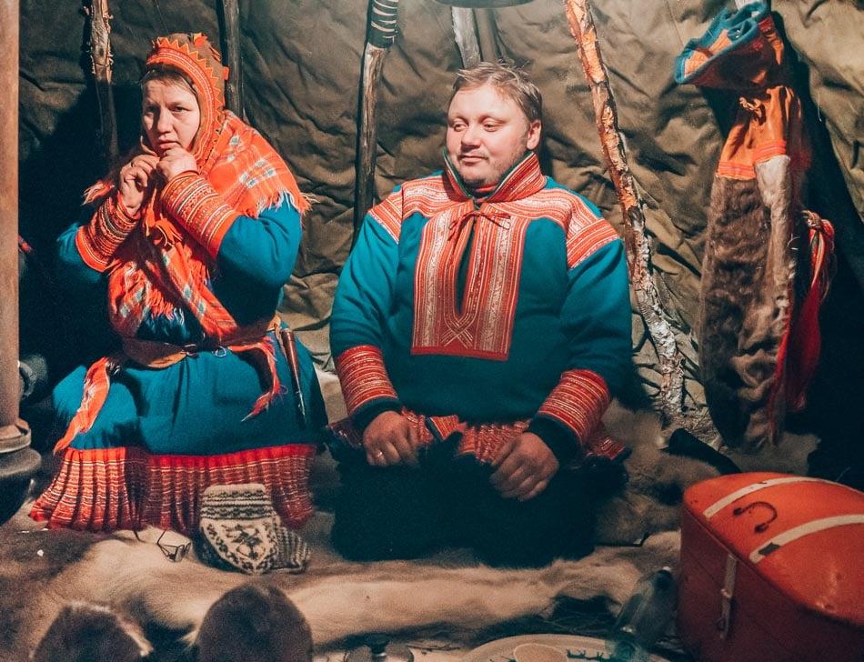 Oddbjørg and Nils Sara, Sami reindeer herders, wearing traditional Sami costume in a Lavvu tent.