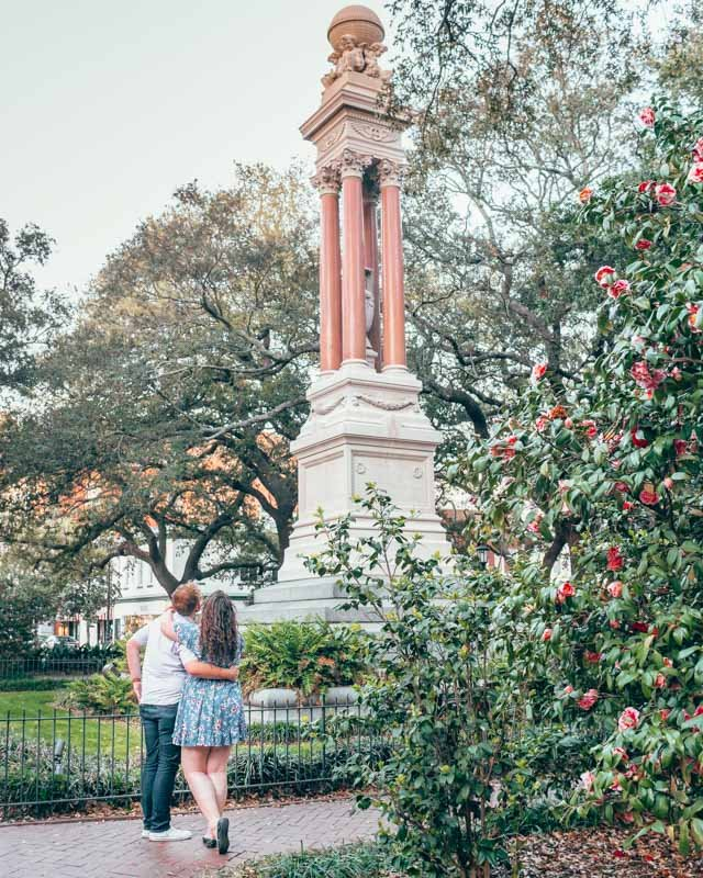 Couple gazing up at a statue in a square in surrounded by lush greenery in Savannah, Georgia