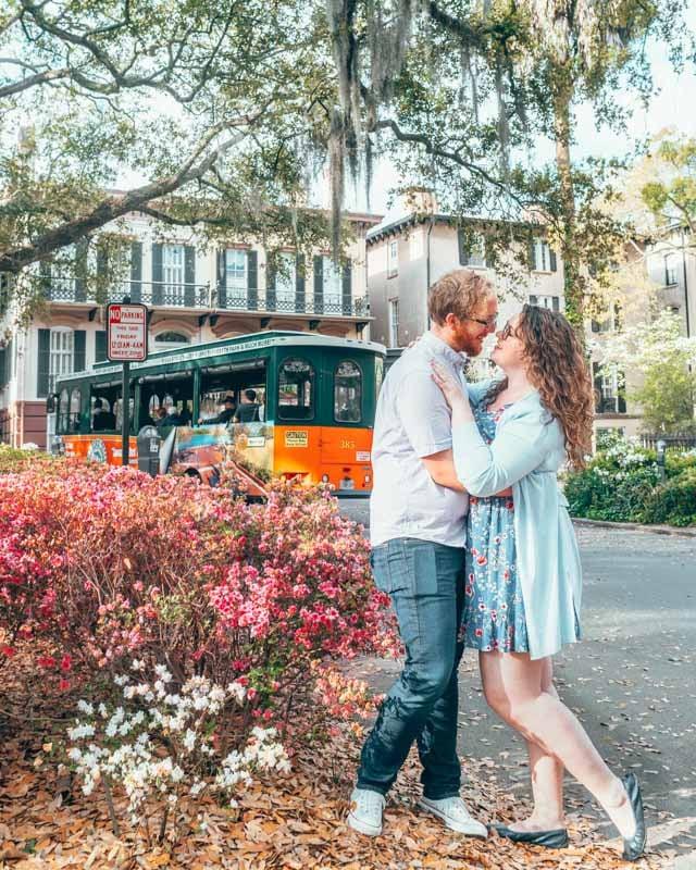 Couple kissing under an oak tree as a trolley rolls past in Savannah, Georgia.