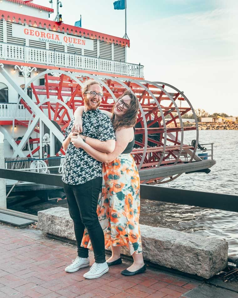 Couple embracing in front of the red paddles of the Georgia Queen steamboat in the river on River Street in Savannah, Georgia.