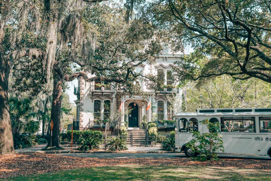 A trolley drives past a historic home in Savannah, Georgia underneath oak trees draped with Spanish moss.
