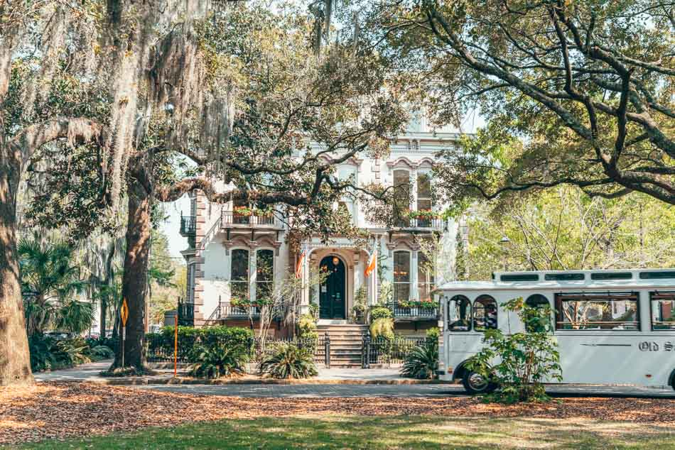 Historic home hidden behind dripping Spanish moss as a trolley passes in front in Savannah, Georgia
